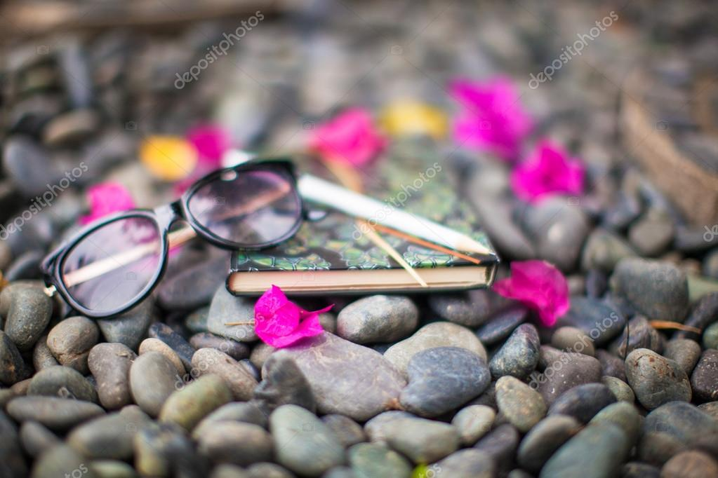 Notepads plans and sunglasses on a gravel road to the sea