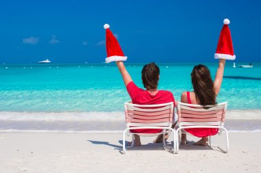 Happy young couple in red Santa Hats sitting on beach chairs