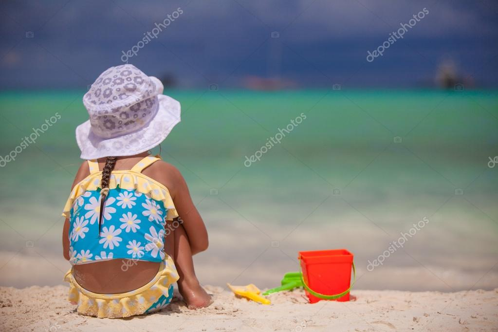 Back view of little girl playing on sandy beach