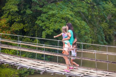 Young mother with her little girls on suspension bridge over the River