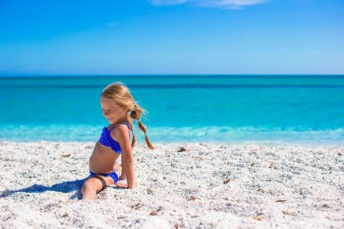 Adorable little sporty girl on white tropical beach