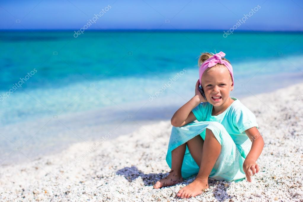 Little adorable girl with cell phone during beach vacation