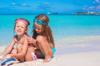 Adorable little girls in swimsuit and glasses for swimming at tropical beach