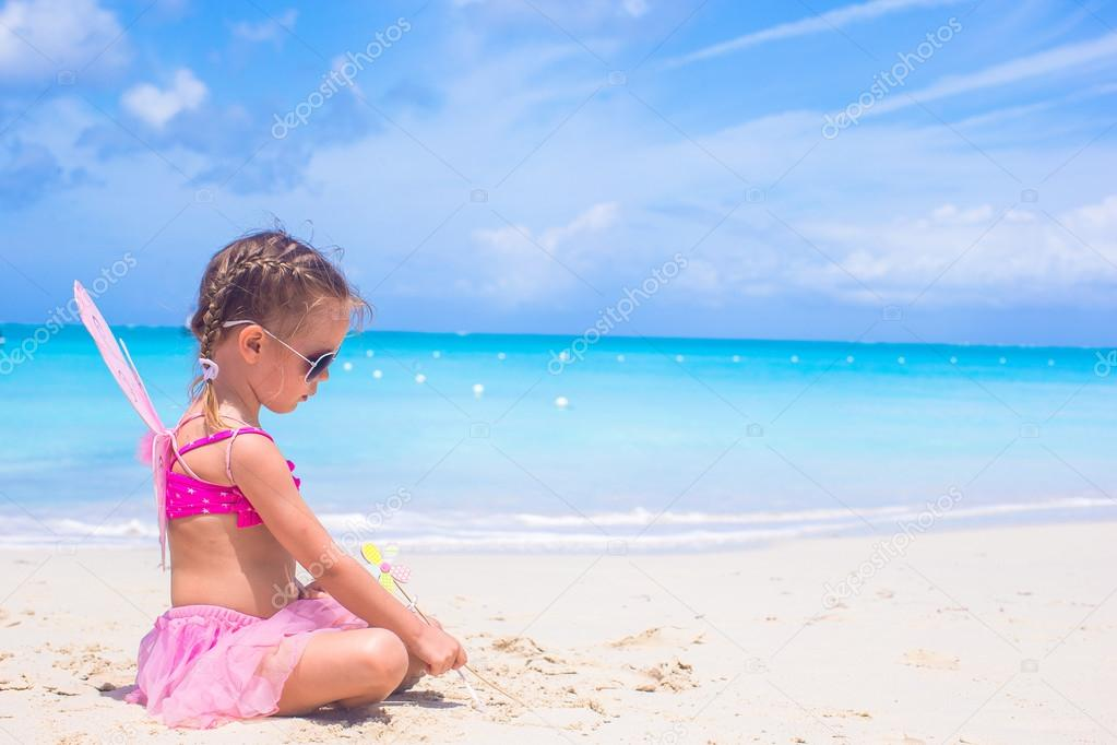 Adorable little girl with wings like butterfly on beach vacation