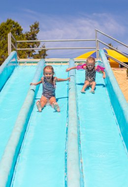 Cute girls on water slide at aquapark during summer holiday