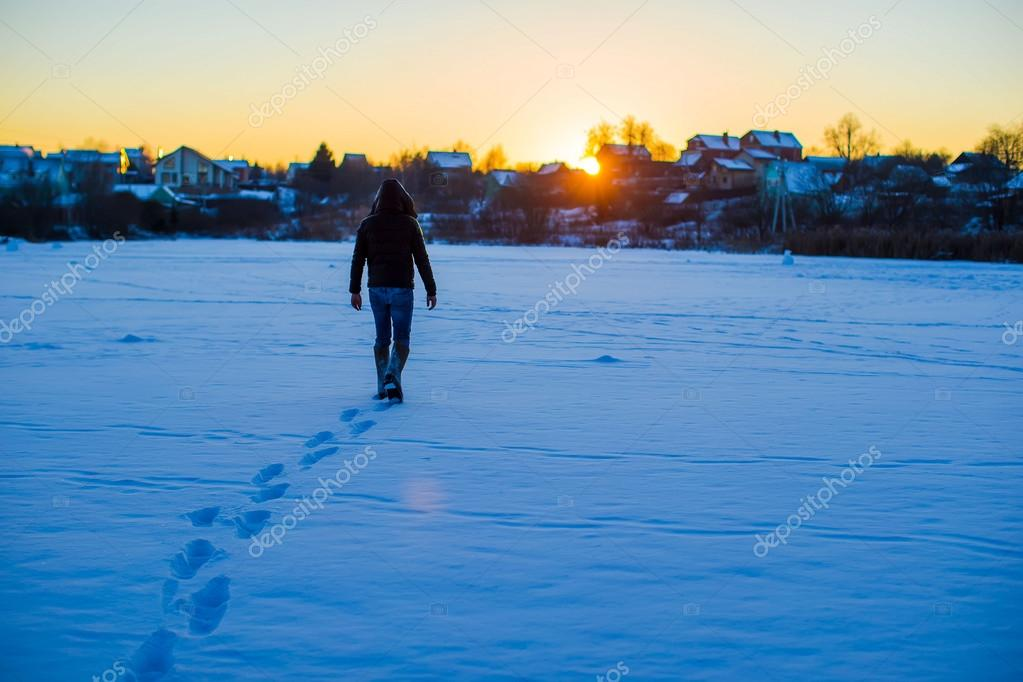 Man walking on deep snowy field