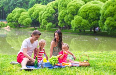 Happy parents and two kids picnicking outdoors