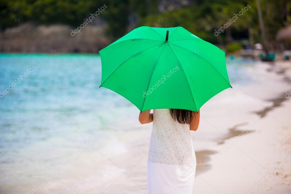 Young girl with umbrella on white beach