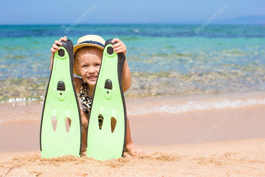 Little girl with flippers and goggles for snorkling on the beach
