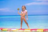 Fotografie Holčička s lízátko se bavit na prkno v moři