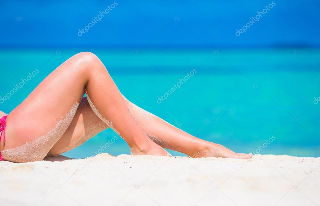 Female slim tanned legs on a white tropical beach