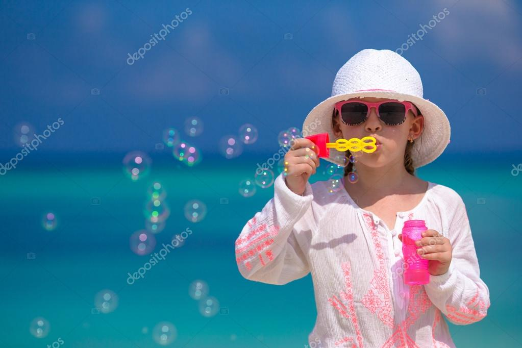 Adorable little girl making soap bubbles during summer vacation