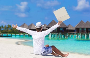Young man with laptop enjoying vacation near water villa