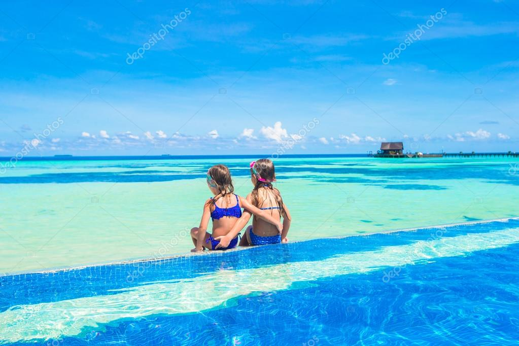 Adorable little girls in outdoor swimming pool