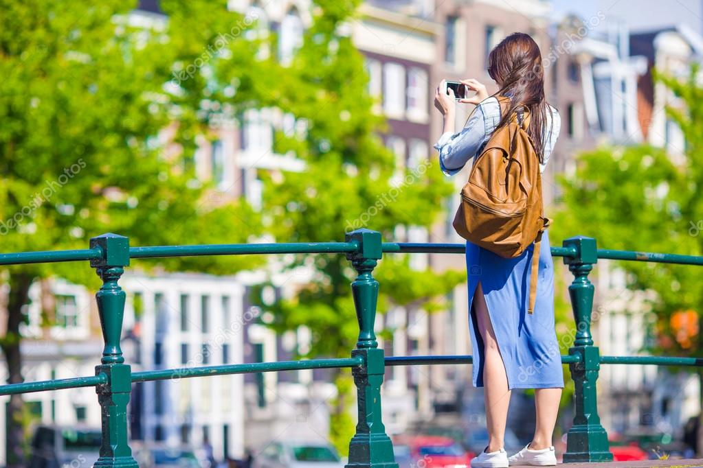 Young woman tourist taking photo on beautiful view of european city with mobile smart phone camera