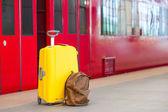 Fotografie Gelbe Gepäck mit Pässen und braun Rucksack am Bahnhof