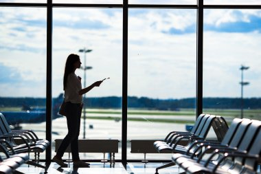 Silhouette of woman in an airport lounge waiting for flight aircraft