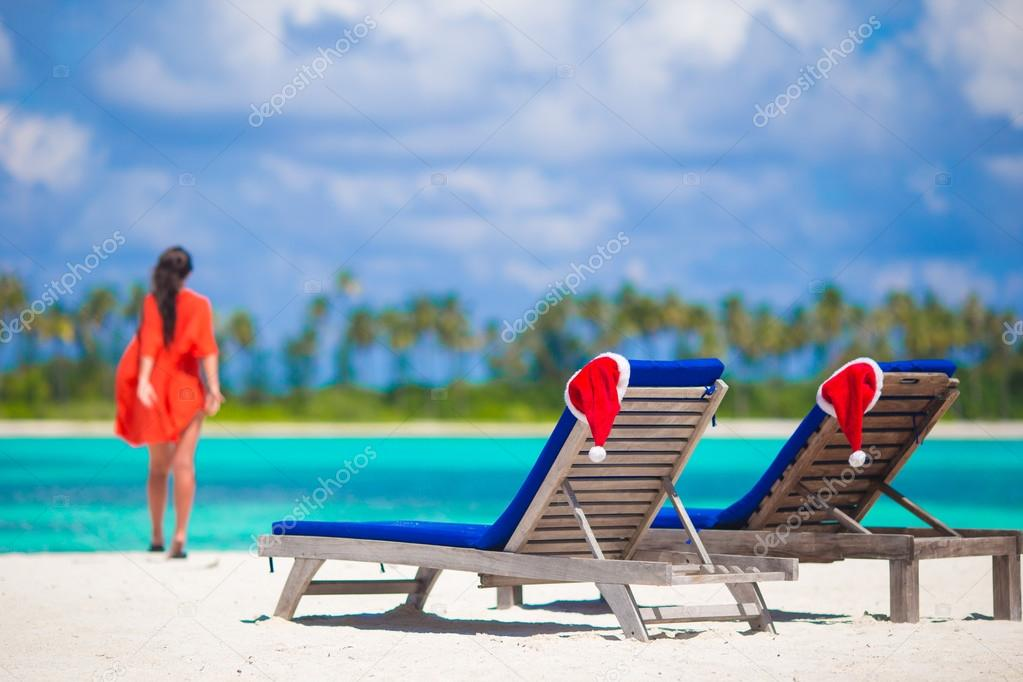 Christmas hats on beach loungers at white beach in Maldives