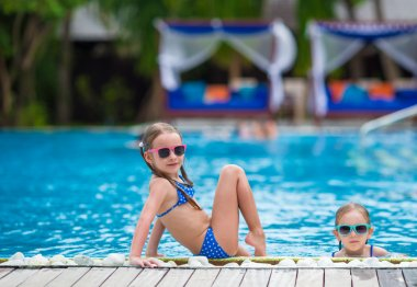 Adorable little girls having fun in outdoor swimming pool on summer vacation