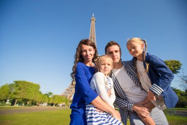 Happy family with two kids in Paris near Eiffel tower. French summer holidays, travel and people concept.