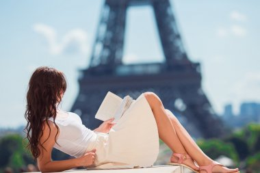 Beautiful woman reading book in Paris background the Eiffel tower