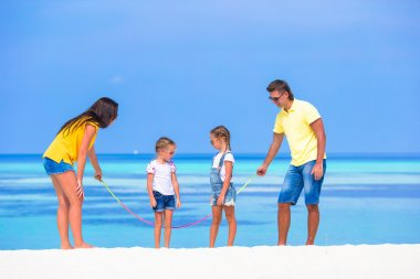 Happy family playing on white tropical beach