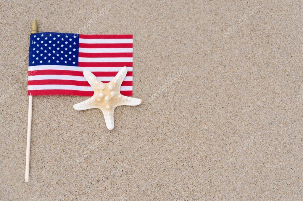 Amrican flag with starfish on the sandy beach