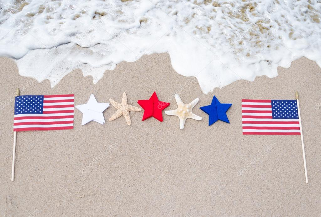 American flags with starfishes on the sandy beach