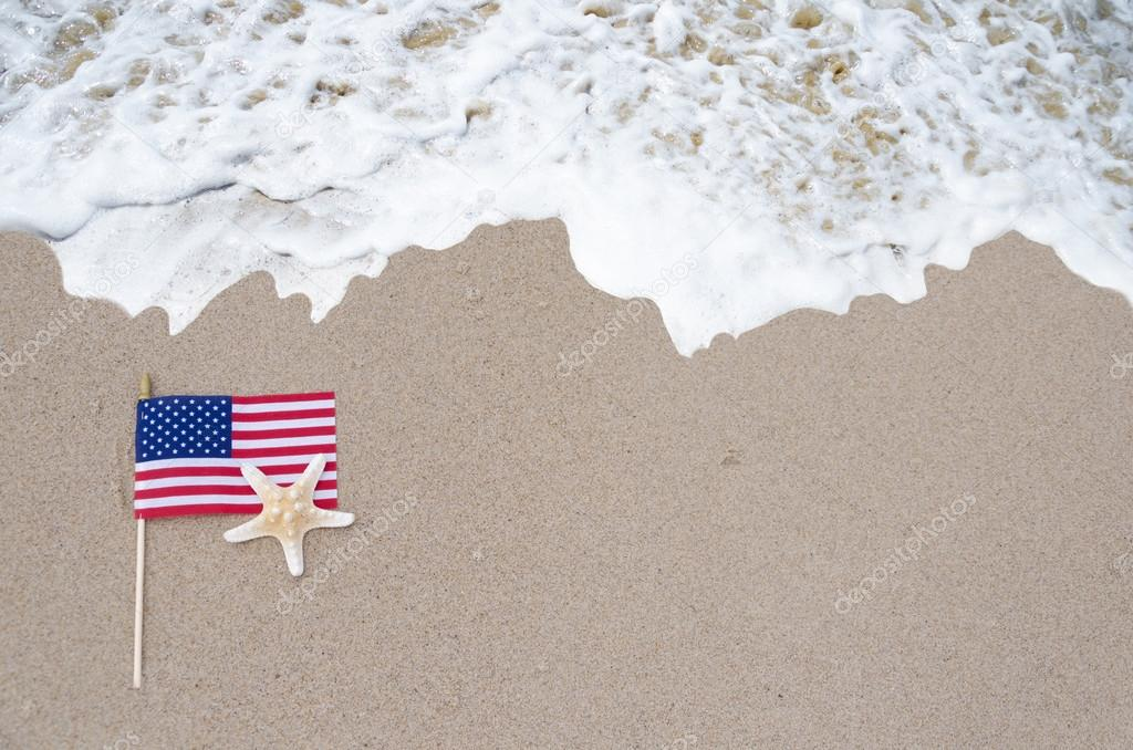 American flag with starfish on the sandy beach