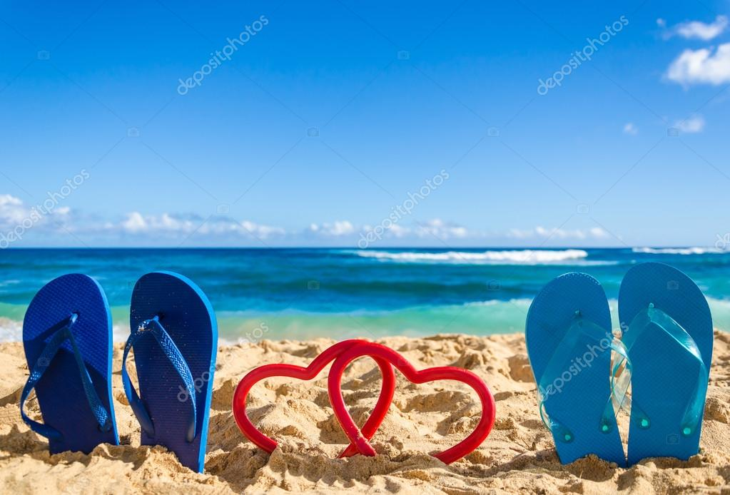 7e097983548f Flip flops with heart shapes on the sandy beach — Stock Photo ...