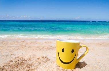 Happy face mug on the sandy beach stock vector