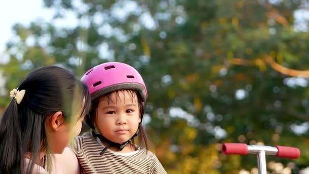 Anya vigasztalja és átöleli a lányát, miután elesett, miközben robogózott a nyári parkban. Aktív szabadtéri sport gyerekeknek.