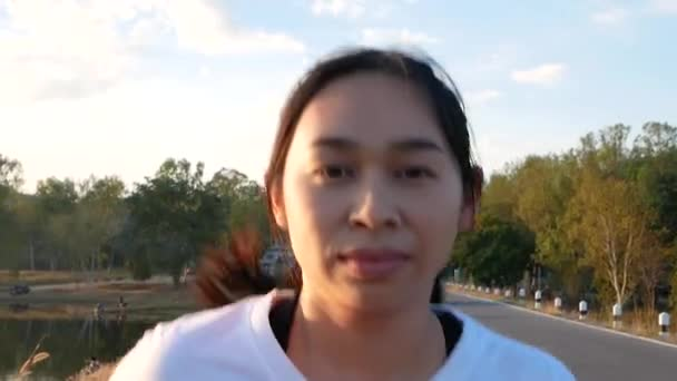 Close up shot of A healthy woman jogging run and workout on sunset lakeside road. Asian runner people exercise outdoor. Health care and Lifestyle Concept.