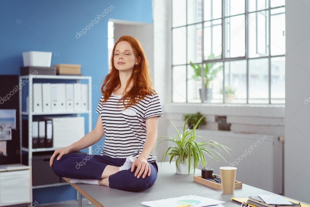 Posizione Scrivania Ufficio : Giovane donna che meditating sulla sua scrivania in ufficio u foto