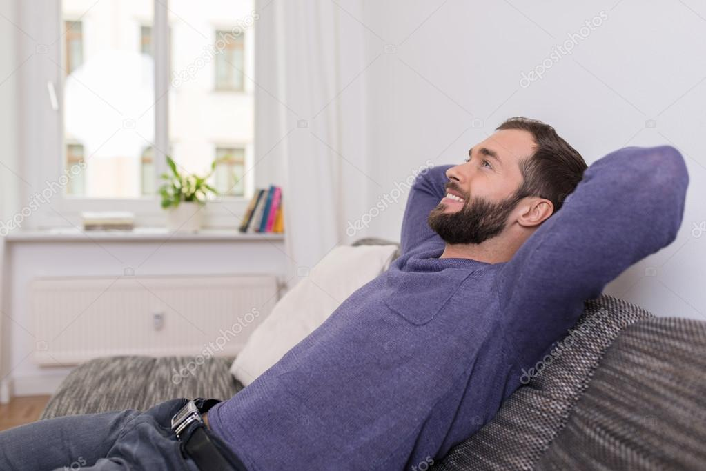 Successful man relaxing on the sofa at home — Stock Photo © racorn ...