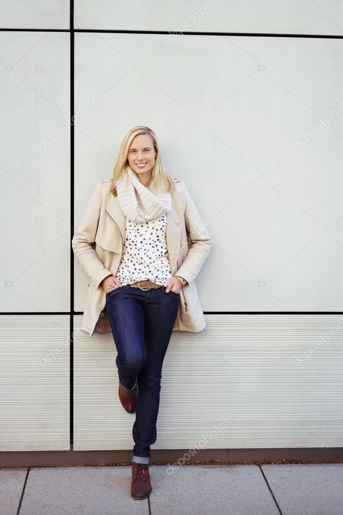 Stylish Young Woman Leaning Against Wall Stock Photo