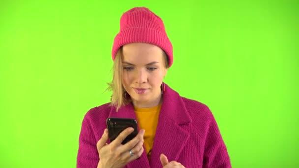 Eine kokette junge fröhliche Frau in rotem Mantel und Hut benutzt ein Handy und tippt eine Nachricht. Eine schöne Kaukasierin tippt auf den Bildschirm ihres Smartphones und lächelt