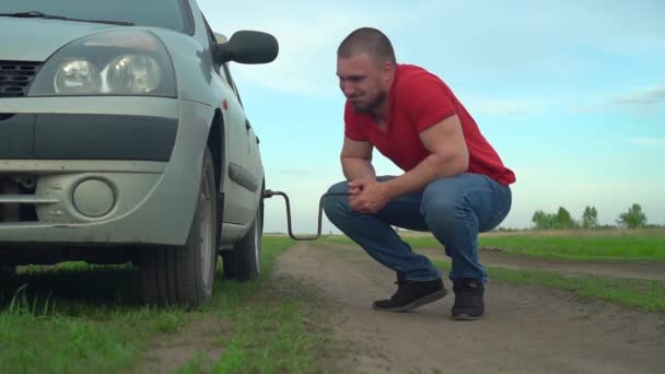 Frustrated Motorist Near Broken Car with Key in Hand. Negative Emotions in connection with the Car Breakdown