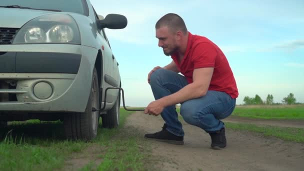 Frustrated Motorist With Broken Car Tries to Diagnose Breakdown, Touches Wheel, Opens Bolts. Self repair concept