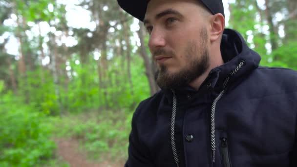 Bärtiger Mann mit Baseballmütze im Wald sieht seitlich aus, verdächtiger Blick.