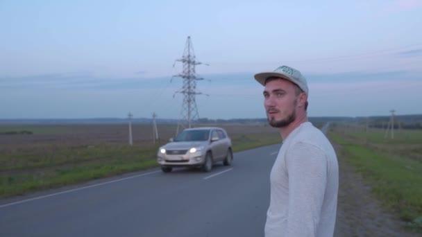 Drzý muž stojí poblíž silnice a plive sliny, rozzlobený muž čeká na taxi. Pomalé vyplivnutí