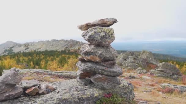 Vyvážené kamínky naskládané na sebe v horském údolí. Hierarchie a rovnováha. Pyramida z kamení na texturovaném nebi a krásných kopcích, hory.
