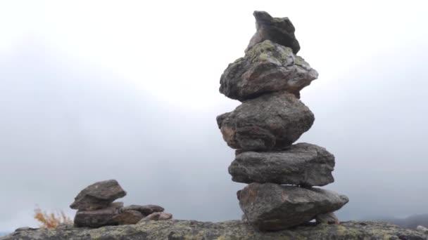 Vyvážené kamínky naskládané jeden na druhém. Hierarchie a rovnováha. Pyramida z kamenů na pozadí mlhavé oblohy