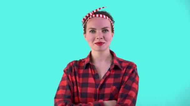 Stilvolle und schöne Hausfrau im Pin-up-Stil hinter dem Rahmen nimmt ein Bügeleisen auf blauem Hintergrund. Hauswirtschaftskonzept, Haushälterin