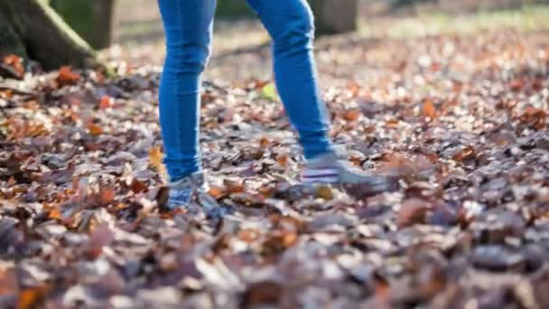 Woman walking over leaves