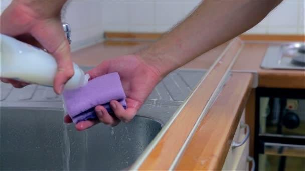 Mann-Putting-Reinigungsmittel auf Schwamm