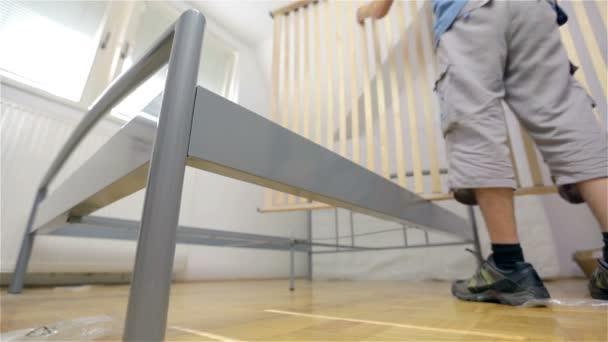 Man Setting up wooden bed slats