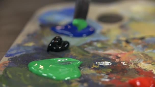 Míchání modré a zelené barvy na paletě