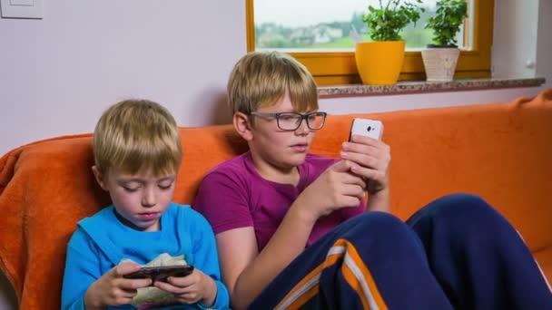Bratři v obývacím pokoji na pohovce hraje