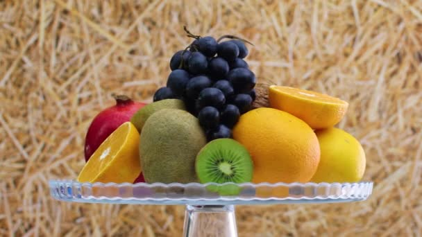 Slowly rotating various kind of fresh ripe fruits on glass crystal bowl